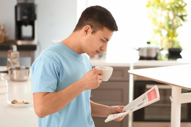Knappe jongeman die de krant leest terwijl hij koffie drinkt in de keuken