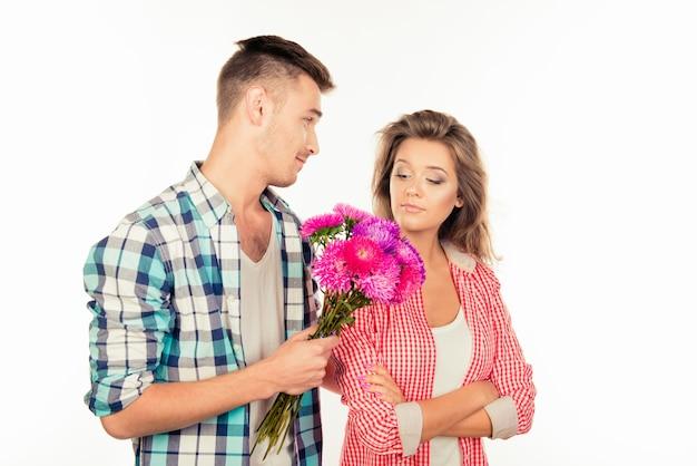 Knappe jongeman die een boeket geeft aan zijn schattige geliefde en vraagt om hem te vergeven