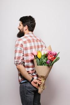 Knappe jongeman die een bos bloemen achter zijn rug houdt en tegen een witte muur staat