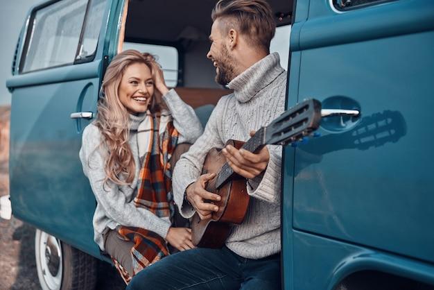 Knappe jongeman die gitaar speelt voor zijn vriendin terwijl hij tijd doorbrengt in de camper
