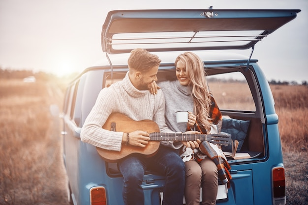 Knappe jongeman die gitaar speelt voor zijn vriendin terwijl ze allebei buiten in de kofferbak zitten