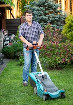 Knappe jongeman die gras maait in de achtertuin van het huis