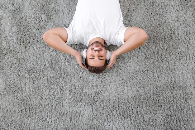Knappe jongeman die naar muziek luistert terwijl hij thuis ontspant