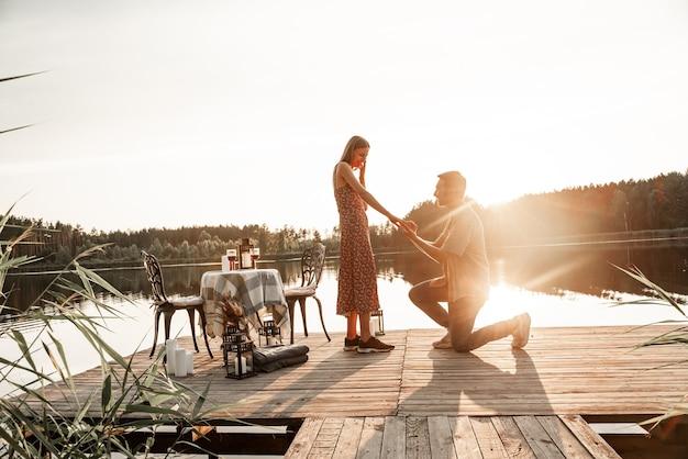 Knappe jongeman die om de hand van een geliefde mooie vriendin vraagt en ten huwelijk vraagt. kerel die tijdens zonsondergang op zijn knie staat en verlovingsring aanbiedt aan verraste vrouw buiten op het bosmeer