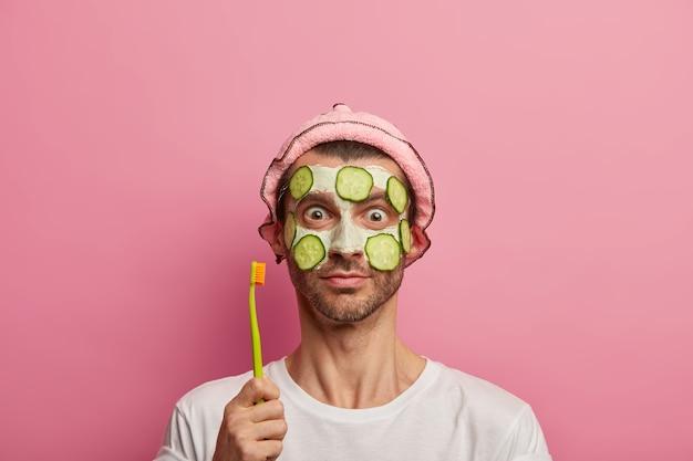 Knappe jongeman draagt kleimasker met komkommers voor huidverzorging, tandenborstel houdt tanden poetsen