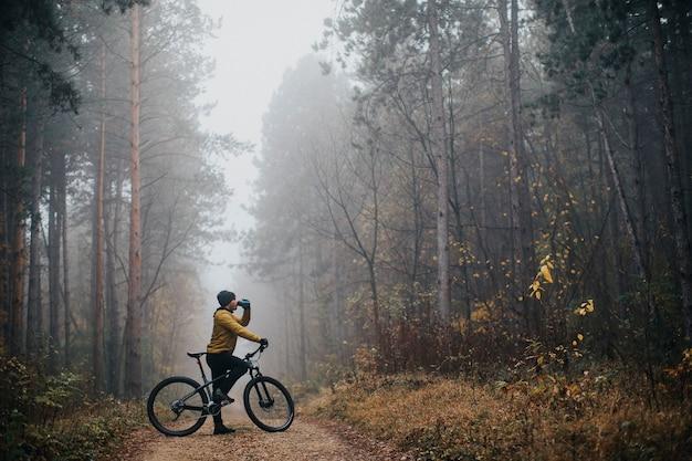 Knappe jongeman een rem nemen tijdens het fietsen door herfst bos