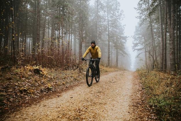 Knappe jongeman fietsen door herfst bos