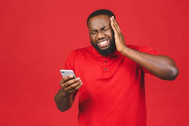 Knappe jongeman, geschokt, verrast, wijd open mond, boos door wat hij op zijn mobiel ziet