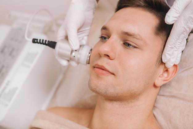 Knappe jongeman huidverzorging behandeling bij schoonheidssalon