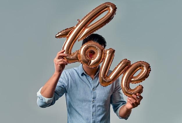 Knappe jongeman in blauw shirt staat met luchtballon met het label liefde in handen op grijs.