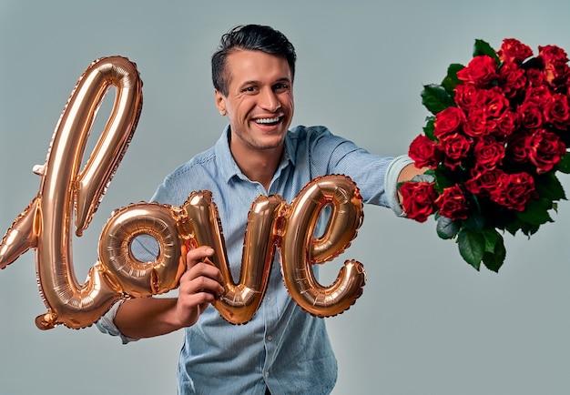 Knappe jongeman in blauw shirt staat met rode rozen en luchtballon met het label liefde in de hand op grijs.