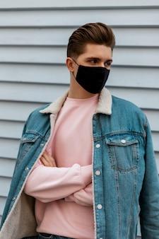 Knappe jongeman in denimblauwe stijlvolle jas in roze sweatshirt in zwart beschermend masker buitenshuis. modieuze man loopt in masker op stad. covid-19 virusbeschermingsconcept. nee tegen het coronavirus
