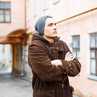 Knappe jongeman in een hoed en jas staan op de binnenplaats van sloppenwijken