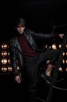 Knappe jongeman in een leren jas in zwarte jeans in rode golf in sneakers poseren binnenshuis staande op de metalen trap tegen de achtergrond van heldere gouden vintage lampen. stijlvol jongensmodel