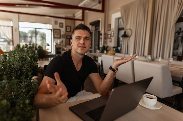 Knappe jongeman in een stijlvol t-shirt met een schattige glimlach met een moderne laptop met een kopje koffie werkt in een café.