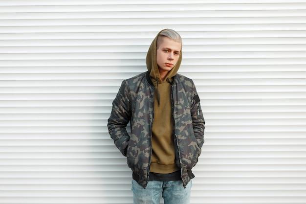 Knappe jongeman in een trendy militair jasje met een capuchon in de buurt van witte metalen jaloezieën