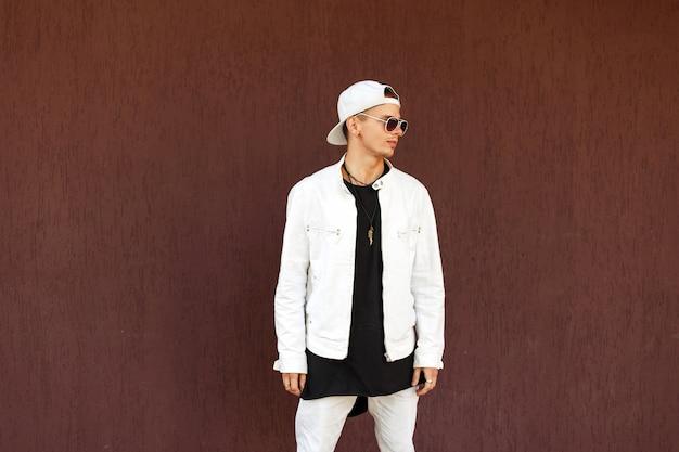 Knappe jongeman in een wit jasje met een baseballpet in zonnebril staat in de buurt van de muur