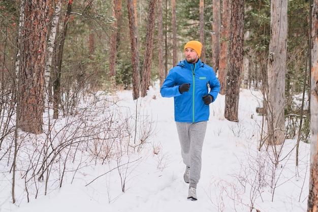 Knappe jongeman in hoed loopt op besneeuwde pad in een prachtig bos tijdens de training alleen