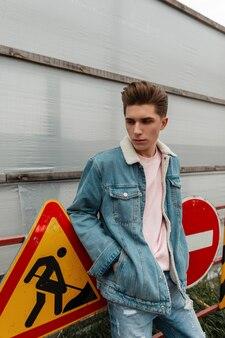 Knappe jongeman in roze stijlvol t-shirt in modieuze blauwe spijkerjas staat in de buurt van metalen verkeersborden op straat. aantrekkelijke man in trendy jeanskleding voor jongeren die in de buitenlucht in de stad poseert. casual herenkleding