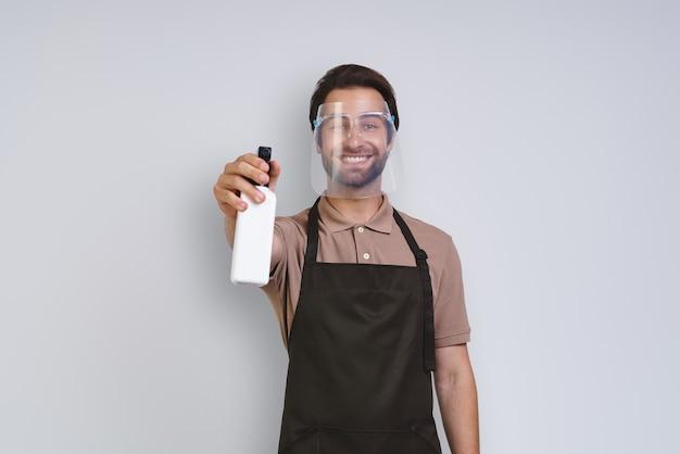 Knappe jongeman in schort die beschermend gezichtsschild draagt en reinigingsspray vasthoudt terwijl hij staat...