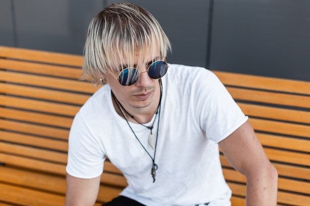 Knappe jongeman in trendy wit t-shirt in stijlvolle blauwe zonnebril met amuletten op een nek zit buiten op een houten bankje. amerikaanse stadsjongen is blond en ontspant in de stad. street style