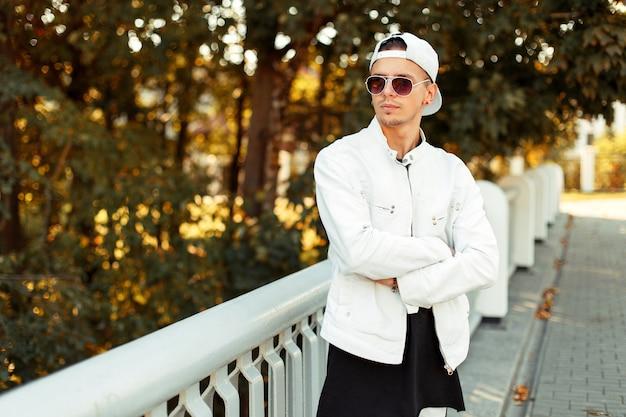 Knappe jongeman in zonnebril in een witte baseballpet en herfst witte jas in de straat op een zonnige dag in de buurt van bomen