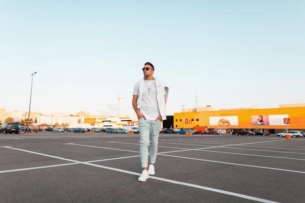 Knappe jongeman in zonnebril in modieuze spijkerbroek in een stijlvol wit t-shirt in sneakers loopt door de stad op een heldere zomerdag. kerel die op straat rust. zomer straatmode.