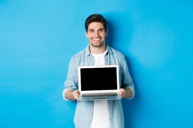 Knappe jongeman introduceert product op laptopscherm, toont computer en glimlacht, staande over blauwe achtergrond