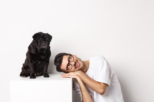 Knappe jongeman lag hoofd in de buurt van schattige zwarte mopshond, glimlachend en kijkend naar kopieerruimte, witte achtergrond