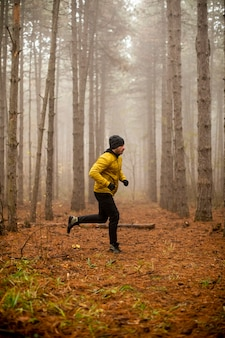 Knappe jongeman loopt in herfst bos en trainen voor trail run marathon endurance race