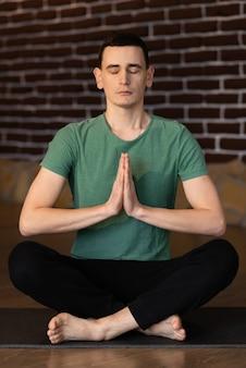 Knappe jongeman mediteren in de woonkamer