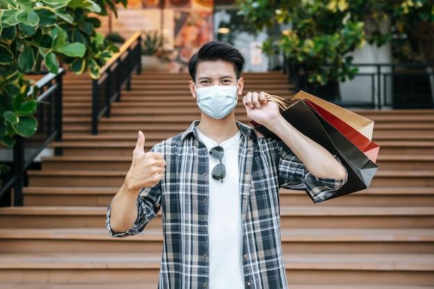 Knappe jongeman met beschermingsmasker houdt meerdere papieren zakken vast