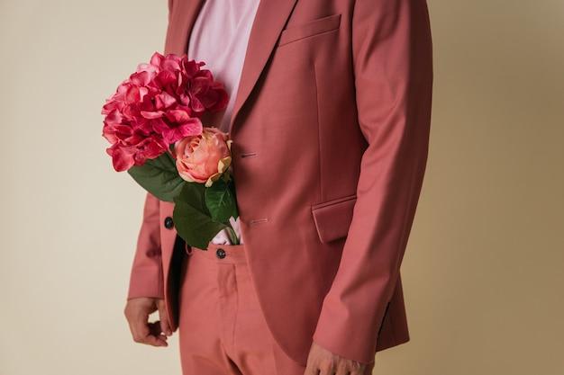 Knappe jongeman met bloemen in zijn broek, gekleed in een roze pak