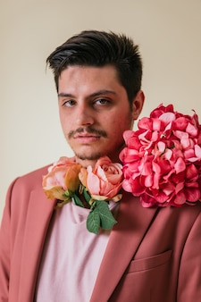 Knappe jongeman met bloemen om zijn nek, gekleed in een roze pak