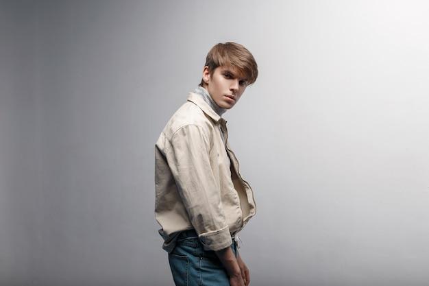 Knappe jongeman met een kapsel in een fel licht stijlvol jasje in blauwe modieuze broek in retro stijl staat binnenshuis tegen een witte muur. stijlvolle knappe jongen. kleding in jeugdstijl