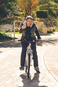 Knappe jongeman met fiets duimen opdagen in park op zonnige dag
