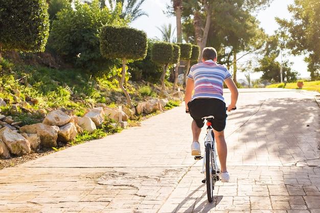 Knappe jongeman met fiets en helm in park op zonnige dag.