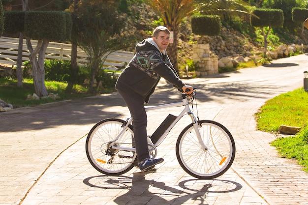 Knappe jongeman met fiets in park op zonnige dag