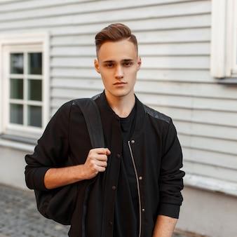 Knappe jongeman met kapsel in een jas met een rugzak in de buurt van een houten huis