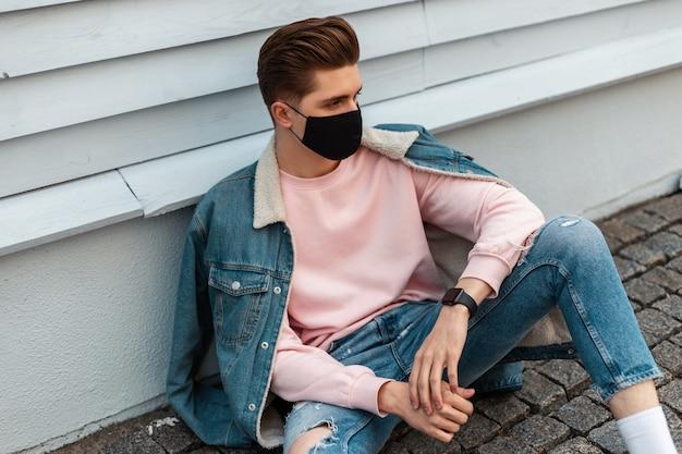 Knappe jongeman met kapsel in modieuze blauwe spijkerjas in spijkerbroek in roze sweatshirt met medisch zwart masker zit op straat in de buurt van vintage gebouw. stijlvol jongensmodel. mode 2020. zomer.