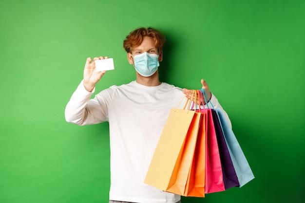 Knappe jongeman met medisch masker, met plastic creditcard en boodschappentassen met artikelen gekocht met korting, groene achtergrond