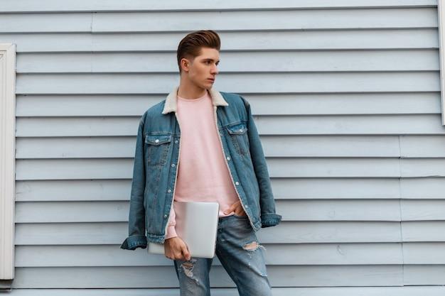 Knappe jongeman met stijlvol kapsel in modieuze casual spijkerbroeken met moderne gadgets in de buurt van vintage gebouw in de stad. mannequin aantrekkelijke man met laptop poses op straat
