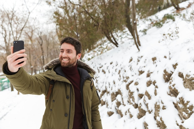 Knappe jongeman met winterjas met behulp van mobiele telefoon tijdens het wandelen buiten, een selfie te nemen