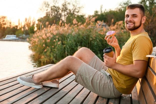 Knappe jongeman met zoete donut en koffie in de buurt van de rivier