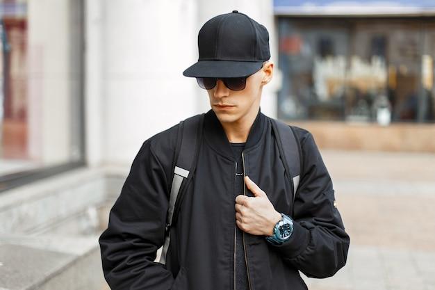 Knappe jongeman met zonnebril in een zwarte jas met een rugzak in de stad