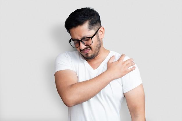 Knappe jongeman met zwarte bril met pijn in de schouder op witte achtergrond