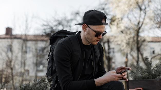 Knappe jongeman model in trendy zonnebril in zwarte casual kleding in pet met rugzak kijkt naar smartphone in straat op zonnige dag. amerikaanse man in mode kleding met telefoon rust in de stad.