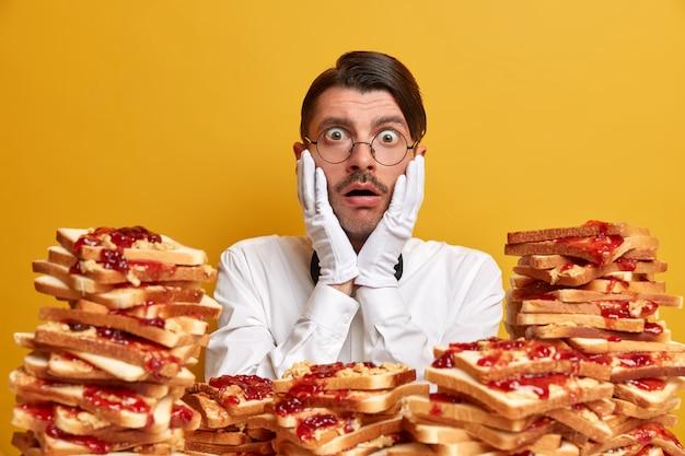 Knappe jongeman omringd door boterhammen met pindakaas gelei