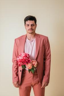 Knappe jongeman op zoek met bloemen in zijn broek, gekleed in een roze pak