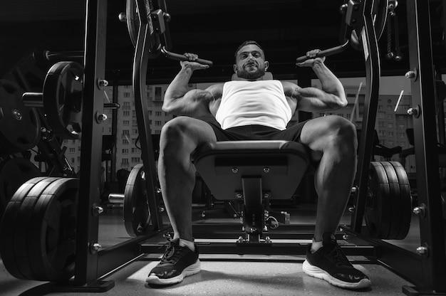 Knappe jongeman pompt zijn schouders in een speciale machine. fitness en bodybuilding concept. gemengde media